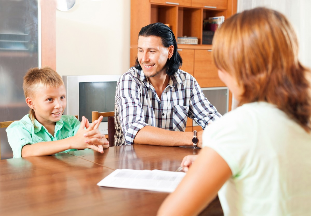 Son and father answer questions of a social worker in home