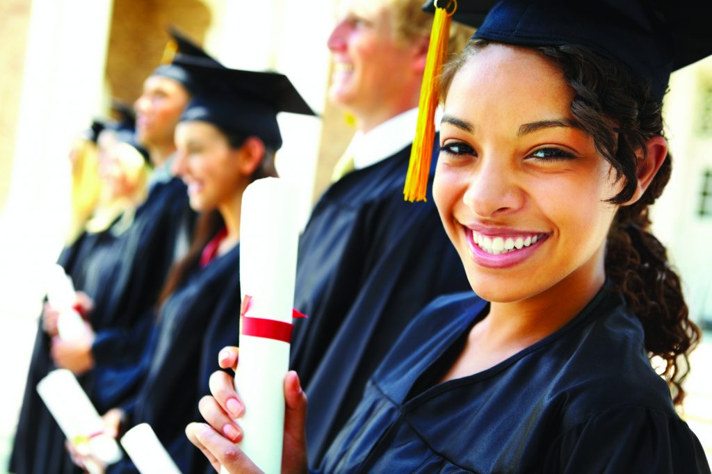 Closeup of beautiful girl with friends in graduate gowns holding certificates